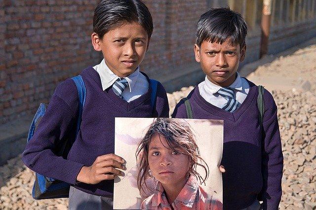被害女性の写真を掲げる少年たち