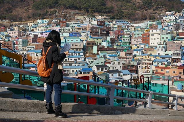 甘川文化村の観光案内所で「スタンプツアーマップ」を眺める観光客